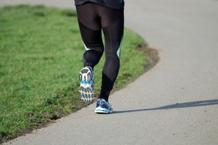Image of a person's legs in black jogging leggings and white and blue running shoes, jogging around a paved track with green grass on the left.