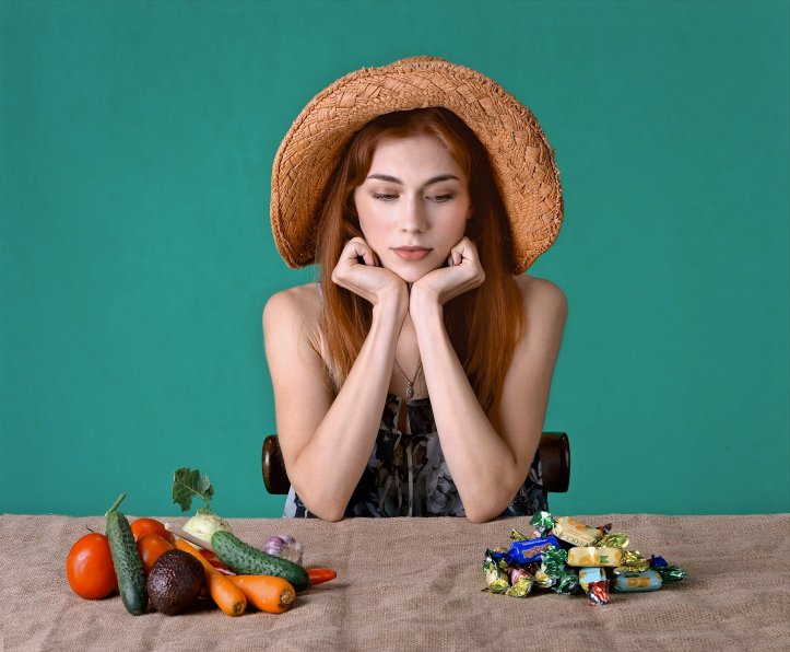 Photo of a red-haired woman sitting at a cloth-covered table. In front of her are a pile of vegetables and a second pile of candy. She has her head resting in her hands and is staring longingly at the pile of candy.